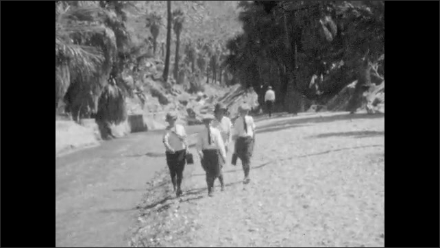 1930s: Man, woman and children skip rocks in creek. Man takes a picture with camera. People in sailor suits walk alongside creek and river.