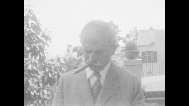 1930s:??Man standing in garden lights cigar and smokes. Boy in suit and cap approaches camera and take cap off and bows.??