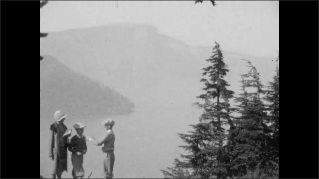 1940s: People stand at mountain overlook. Woman and boys stand in front of mountain and lake. Building at base of mountain.