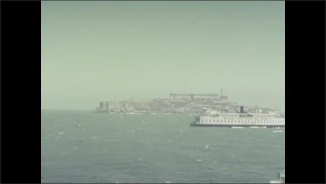 1940s: Boats move through water.  Prison on island.  Bridge.