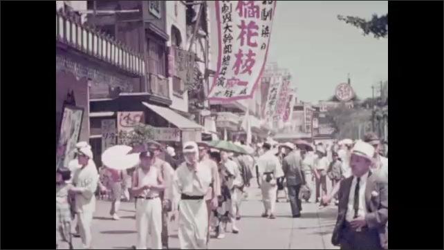 1940s: People walk down city street.  Boys play in water.