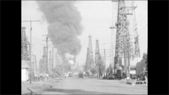 1940s: Car drives down dirt road in oil field towards fire. Smoke billows into the air.