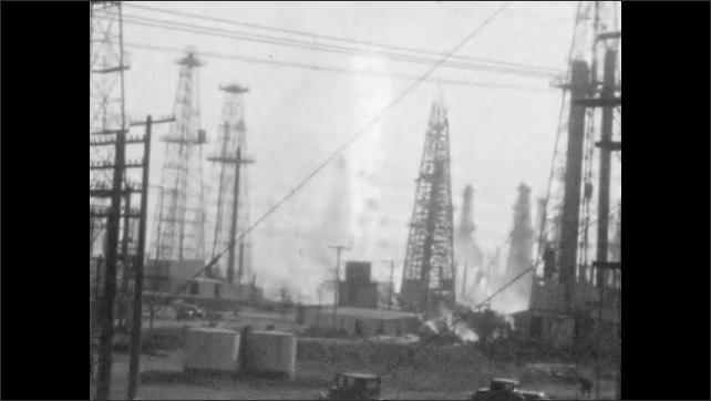 1940s: Flames shoot up from in between oil derricks.