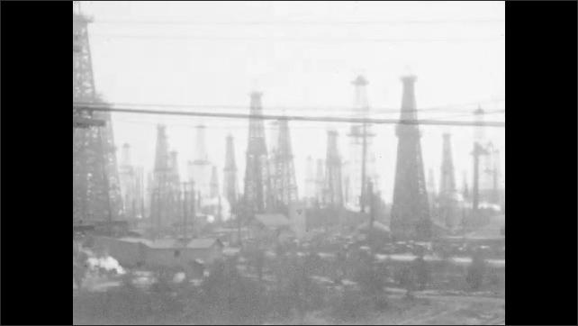 1940s: Men look at flames shooting up from oil derrick. Oil derricks in oil field.