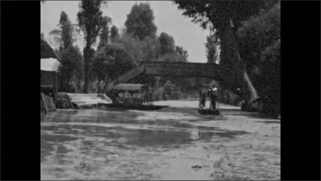 1940s: UNITED STATES: Xochimilco and Floating Gardens in Mexico. View across city. Boat trip along river.