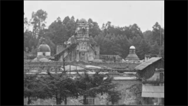 1940s: UNITED STATES: visit to ruins. Couple walk in walled garden. People in market in street.