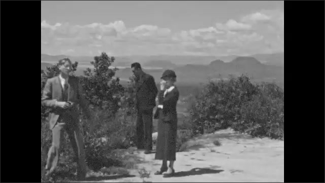 1940s: UNITED STATES: view across landscape towards mountains. Family stand on view point. Railway station in Mexico.