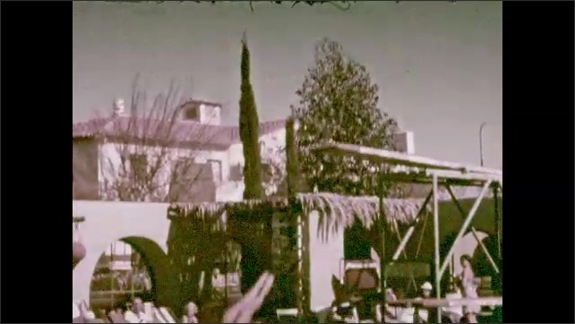 1940s: Man dive off high diving board into pool.
