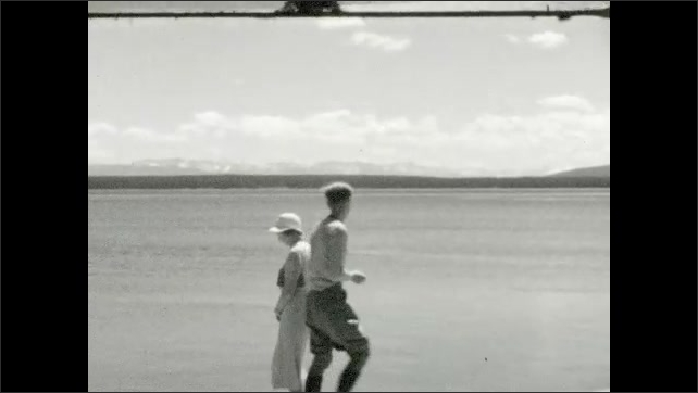 1930s: UNITED STATES: Yellowstone Lake is 26 Miles Across title. People stand by geysers. Lady and boy by water. Boy skims water with stone.