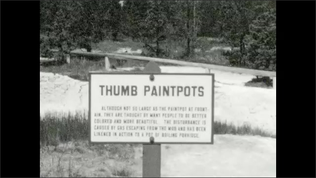 1930s: UNITED STATES: steam above water. Boy stands near geyser. Thumb Paintpots sign. Foaming water