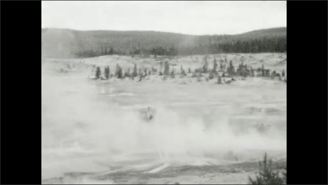 1930s: UNITED STATES: Norris Geyser Basin sign. View across geysers. Steam above ground