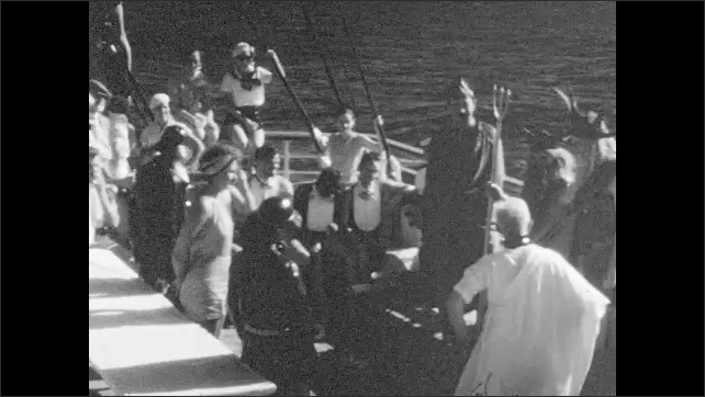 1930s: People perform play on cruise ship, man sits on chair. Actors reads scroll, grab woman, beat her, lift her onto table.