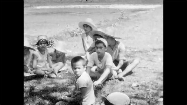 1930s: Women and man stand together, woman throws object. Children sit on grass by ocean. Children run along jetty. Boat full of people travels across ocean.