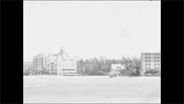 1930s: Big fish swims underwater in aquarium. Buildings along the beach with palm trees around. Ocean waves, building by the beach with palm trees around.