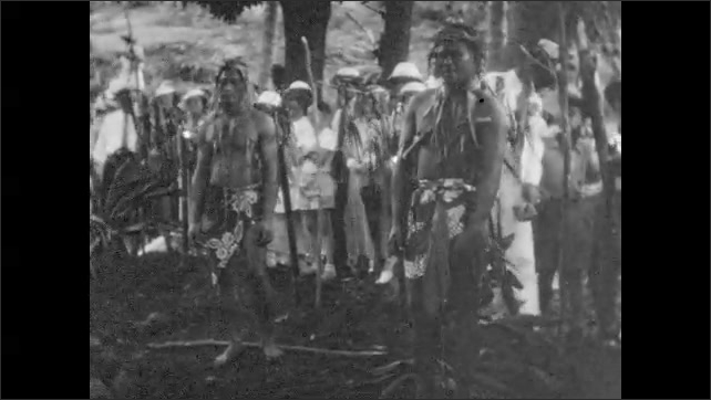 1940s: Men use sticks to move object over smoking boulder pit, man drops pole and object. Crowd watches. Men stand in native island dress. Mountainous islands, boats go out to sea.