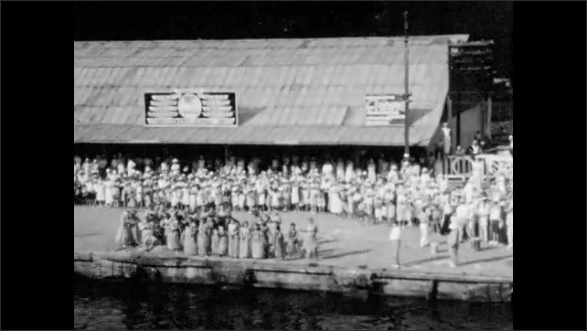 1940s: Dense crowd watches people in native dress, grass skirts dance by canal. People on boat nearby. Foggy mountains.