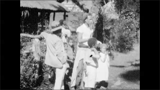 1940s: Dense vegetation, thatched hut, palm trees, native people stand around, woman slaps child. Old man with beard smokes.