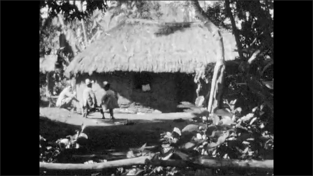 1940s: Village, thatched hut, dense vegetation, young child stands on fence, man in hat stands nearby. People sit on bench, wave. Women lean on building, dresses billow in breeze.