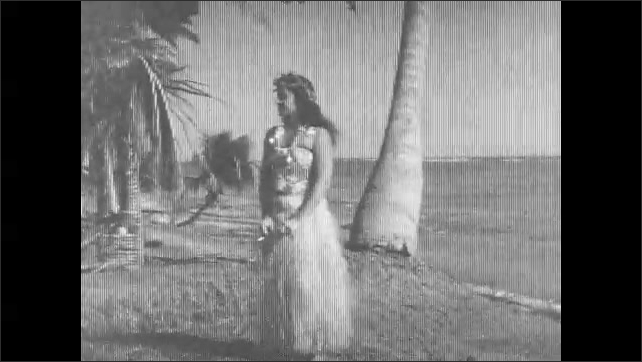 1930s: Sign advertising South Seas Exploration Cruise. Woman in hula skirt stands holding cigarette. Two women and two men stand together on beach. Two boys stand leaning against tree.