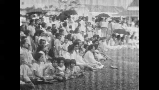 1930s: Large group of women and men dance in row. Audience sits and watches people dance. Women dance in a row.