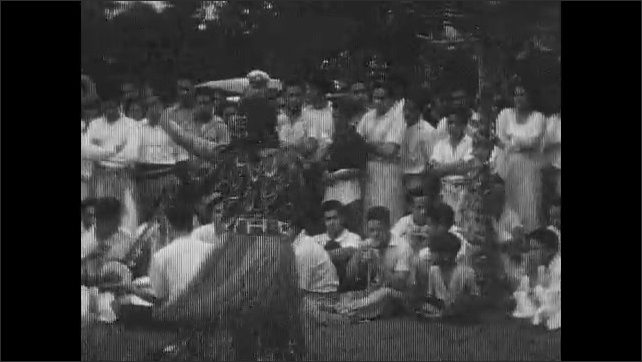 1930s: Women in grass hula skirts dance for audience. Brass band stands in circle playing instruments.