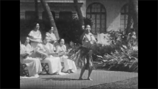 1930s: Two rows of women, one seated and one standing, play ukuleles. Woman in grass skirt hula dances as women play ukuleles.
