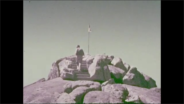 1930s: Man sits atop mountain, mountain range on horizon and valley below. People climb stairs on top of mountain and approach flag. Valley and roads carved into mountainside.