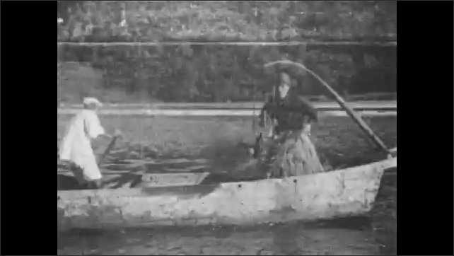 1930s: River by steep mountains, man on boat holds many strings tied to necks of cormorant birds swimming in river. Man lifts heavily smoking basket on pole over end of boat, pulls birds on strings.