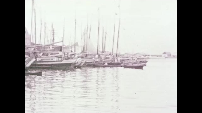 1940s: Sailboats and watercraft moored on the water. People walking on busy city street. Man and boy walk with baskets on their head.