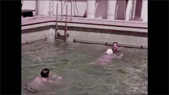 1940s: Men and woman splash and swim in pool.