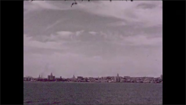 "1940s: Men and woman splash and swim in pool. Intertitle reads ""Havana, Cuba. It was a hot place"". Skyline of Havana from ocean on boat."