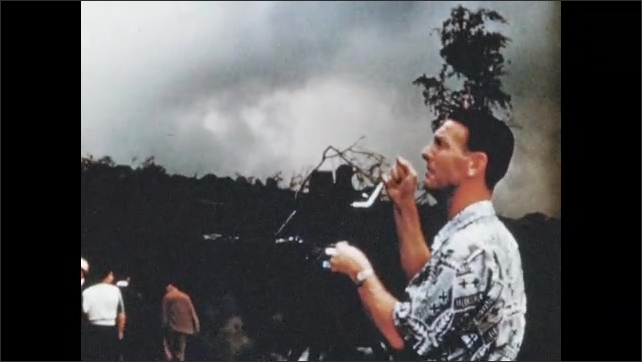 1950s: Bright red lava flow with islands of rock/earth. Man operates film camera as smoke rises on horizon, people stand around. Lava flows into sinkhole, heat radiating.