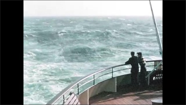 1950s: Passengers look at waves and wake from bow of ship.