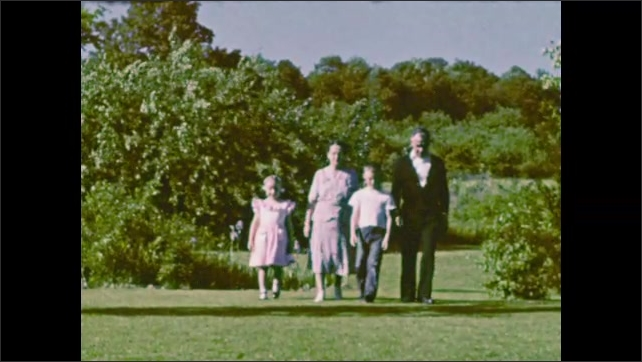 1940s: UNITED STATES: slow motion of family walking in garden. Parents with children.
