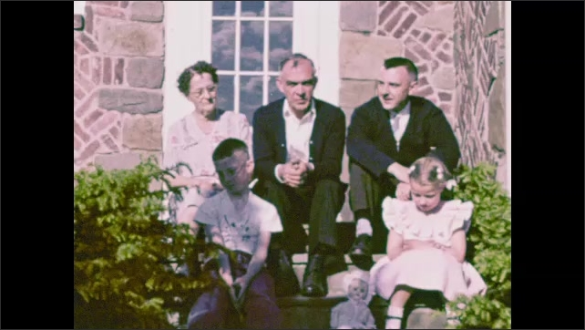 1940s: UNITED STATES: family walk in garden. Family sit on steps and pose for camera. Children stand with parents