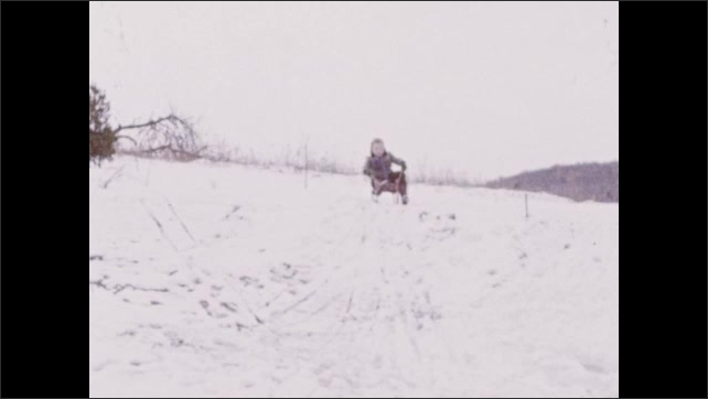 1940s: UNITED STATES: boy with sledge in snow. Boy sits on sledge
