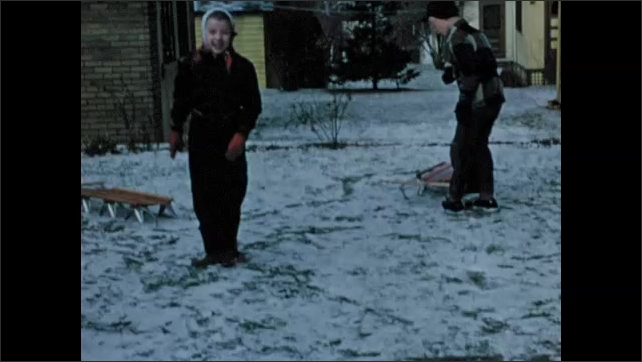 1950s: Small frog in hand. Frog hops off hand. Children play outside with sleds and dog.