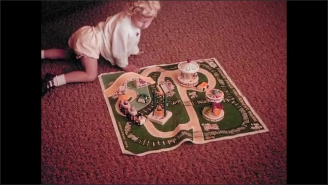 1960s: UNITED STATES: child plays with activity mat on carpet. Fairground activity mat.
