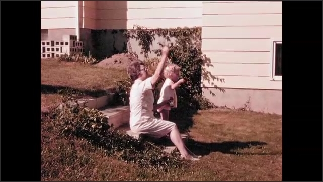 1960s: UNITED STATES: lady and child blow bubbles in garden. Child and grandmother.