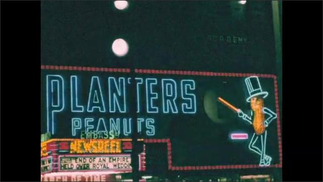 New York City 1940s: Planters Peanuts advert on sidewalk at night. Newsreel advert in lights. Nescafe advert in lights. Canada Dry Water advert