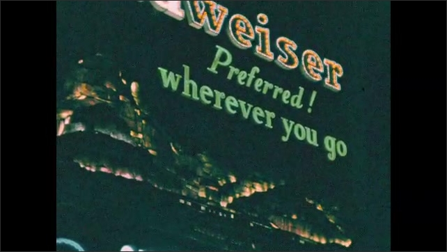 New York City 1940s: Preferred! Wherever you go advert on building. Camel cigarettes advert in lights. Budweiser advert in lights. French Police ordered to fire on mobs headline in lights