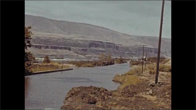 1940s: View of river. Long shots of river, gorge. Car on road, tilt up to cliffs.