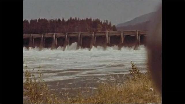 1940s: Long shots of Bonneville Dam. Water flowing through dam. Close up of dam.