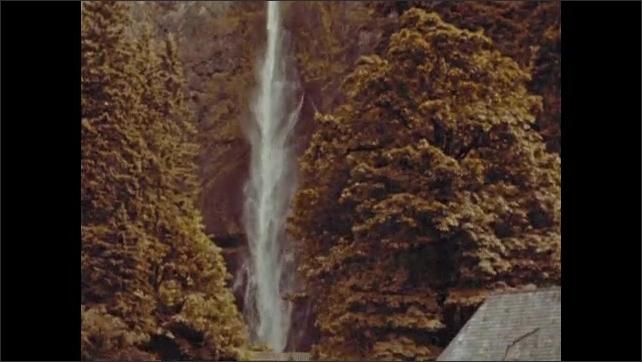 1940s: Tilting shots down waterfall. View of bridge by waterfall.