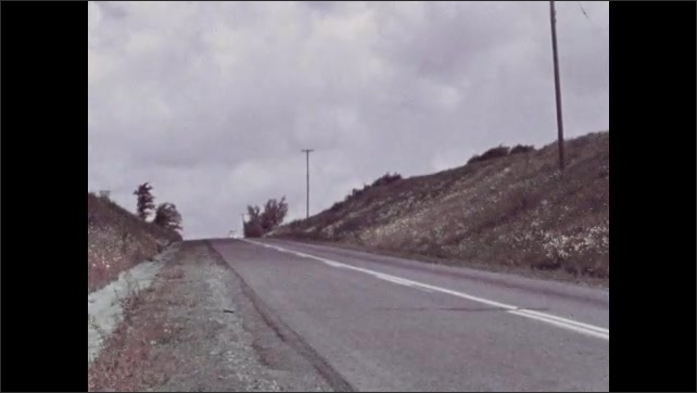 1940s: UNITED STATES: cars pass on road. Clouds in sky. Flowers in meadow.