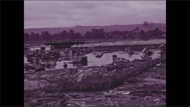 1940s: Flooded homes and buildings.  Mountains.