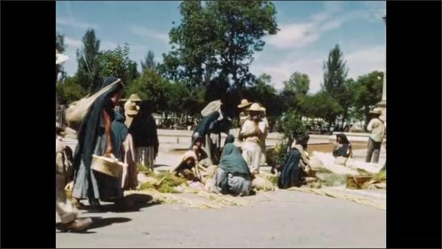 1940s: People walking through market. People in market. Women sitting with plants in market. Women sitting in market.