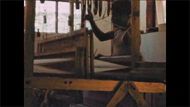 1940s: Pan across fence, wood structure. Man weaving on loom. Fruit hanging in tree.