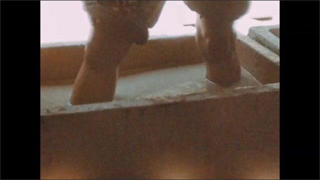 1940s: Man spinning wheel, Close up of man's knees. Legs standing in tub of liquid. Liquid flowing into container.