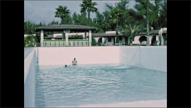 1940s: Resort.  Woman sits in rocking chair.  Young men play in pool.